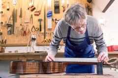 Homem que mede o pescoço de uma guitarra Fotografia de Stock Royalty Free