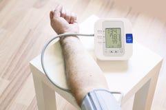Homem que mede sua pressão sanguínea Fotografia de Stock Royalty Free
