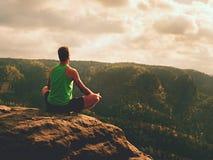 Homem que medita em Lotus Pose no penhasco rochoso Ioga praticando do desportista na borda de pedra fotografia de stock