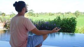 Homem que medita a ioga no jardim exótico filme