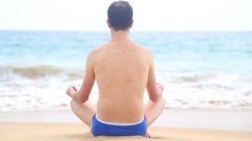 Homem que medita sobre o Sandy Beach nos trópicos video estoque