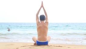Homem que medita sobre o Sandy Beach nos trópicos vídeos de arquivo