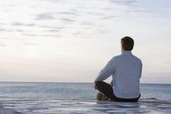 Homem que meditating no mar Imagem de Stock Royalty Free