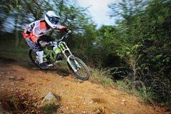 Homem que monta um estilo em declive da bicicleta de montanha Fotografia de Stock