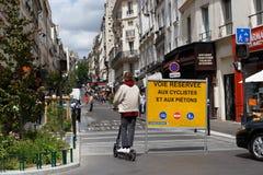 Homem que monta um 'trotinette' elétrico em Paris, Fance em uma zona pedestre fotografia de stock royalty free