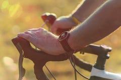 Homem que monta uma bicicleta com o monitor da frequência cardíaca do smartwatch foto de stock