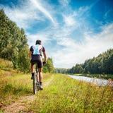Homem que monta uma bicicleta no banco de rio Foto do verão foto de stock royalty free