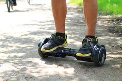 Homem que monta uma placa elétrica do pairo do 'trotinette' fora -, roda de equilíbrio esperta, 'trotinette' do giroscópio, hyros fotografia de stock