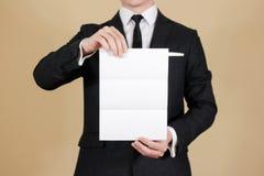Homem que mostra a brochura preta vazia do folheto do inseto Presenta do folheto Imagens de Stock