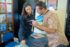 Homem que mostra a fotografia do agente de viagens na câmara digital fotografia de stock royalty free