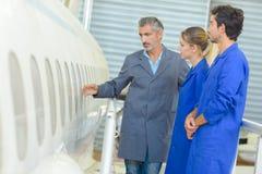 Homem que mostra a fuselagem de aviões aos estudantes foto de stock