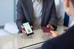 Homem que mostra o bilhete eletrônico do voo fotografia de stock