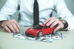 Homem que mostra o carro vermelho com cem dólares Imagem de Stock Royalty Free