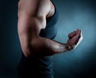Homem que mostra seu bíceps fotografia de stock