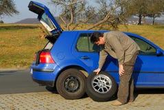 Homem que muda um pneu Foto de Stock