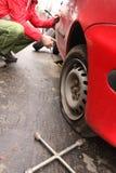 Homem que muda um pneu na rua imagens de stock