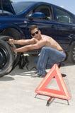 Homem que muda uma roda de seu carro Imagem de Stock Royalty Free