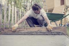 Homem que nivela o cimento em um quintal imagens de stock