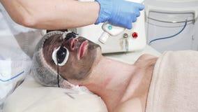 Homem que obtém a casca facial do carbono na clínica da beleza pelo cosmetologist profissional video estoque