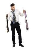 Homem que obtém a escolha vestida entre muitas gravatas Fotografia de Stock