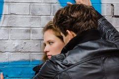 Homem que obtém mais perto da amiga que inclina-se na parede Imagem de Stock Royalty Free
