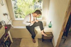 Homem que obtém vestido no banheiro Homem que obtém mudado em casa imagem de stock royalty free