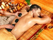 Homem que obtem a massagem de pedra da terapia. Imagens de Stock Royalty Free