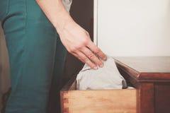 Homem que obtém o roupa interior da gaveta Fotografia de Stock