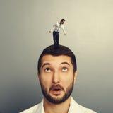 Homem que olha acima no homem novo pequeno Fotos de Stock