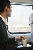 Homem que olha através da janela do trem ao agitar seu café fotos de stock