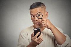 Homem que olha através da lupa no telefone esperto Fotos de Stock