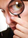 Homem que olha através de uma lupa Imagens de Stock