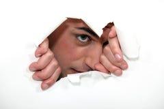 Homem que olha através do furo Imagem de Stock Royalty Free