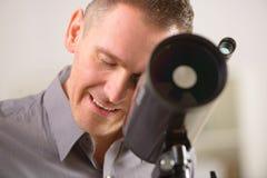 Homem que olha através do telescópio fotografia de stock royalty free