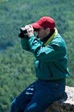 Homem que olha através dos binóculos Fotografia de Stock