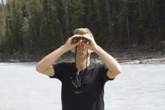 Homem que olha através dos binóculos Imagem de Stock