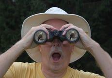 Homem que olha através dos binóculos Fotografia de Stock Royalty Free