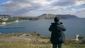 Homem que olha através dos binóculos na baía vídeos de arquivo