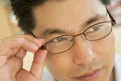 Homem que olha através dos vidros novos Fotografia de Stock Royalty Free