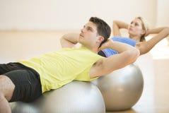 Homem que olha ausente ao exercitar na bola da aptidão no Gym fotos de stock