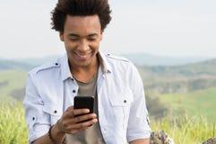 Homem que olha de datilografia no telefone imagem de stock