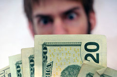 Homem que olha fixamente em um wad do dinheiro Fotografia de Stock