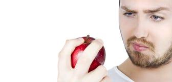 Homem que olha fixamente em uma maçã Imagens de Stock Royalty Free