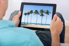 Homem que olha a foto da praia na tabuleta Foto de Stock
