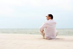 Homem que olha longe perto do mar Fotos de Stock Royalty Free