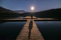 Homem que olha a lua na doca no assobiador Fotografia de Stock Royalty Free