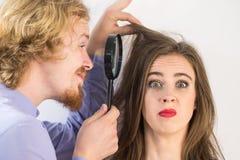 Homem que olha o cabelo da mulher atrav?s do magnifer foto de stock