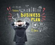 Homem que olha o esquema colorido do plano de negócios Fotos de Stock