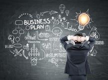 Homem que olha o esquema do plano de negócios Foto de Stock Royalty Free