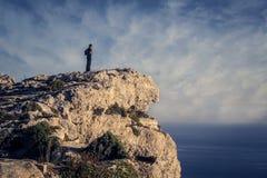 Homem que olha o horizonte de uma rocha Fotos de Stock Royalty Free